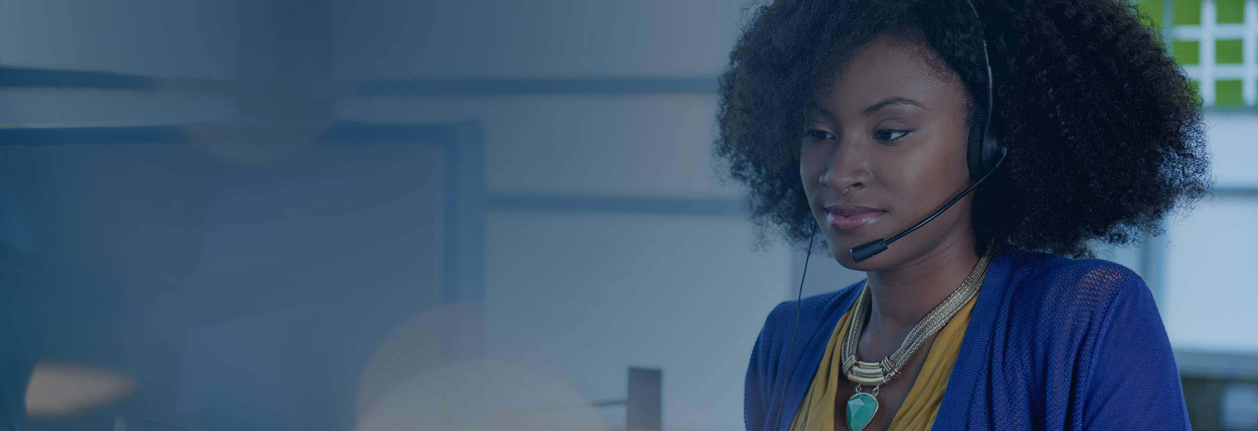 African American woman working using a inbound call center platform wearing a headset