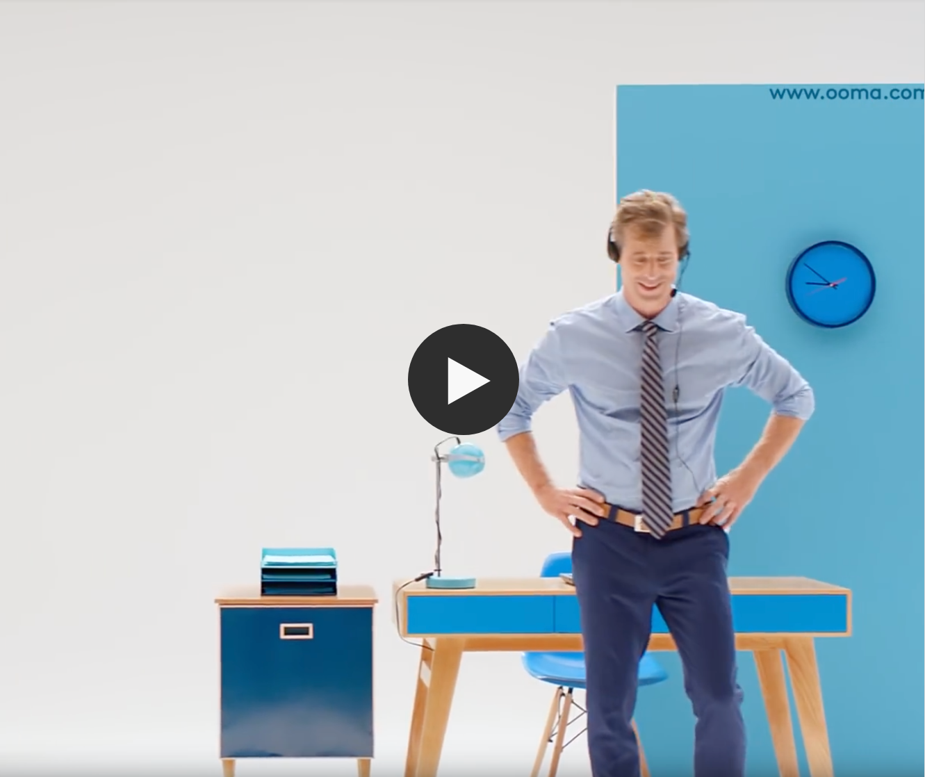 A man standing with a headset in front of a desk - ooma telo device video overview image