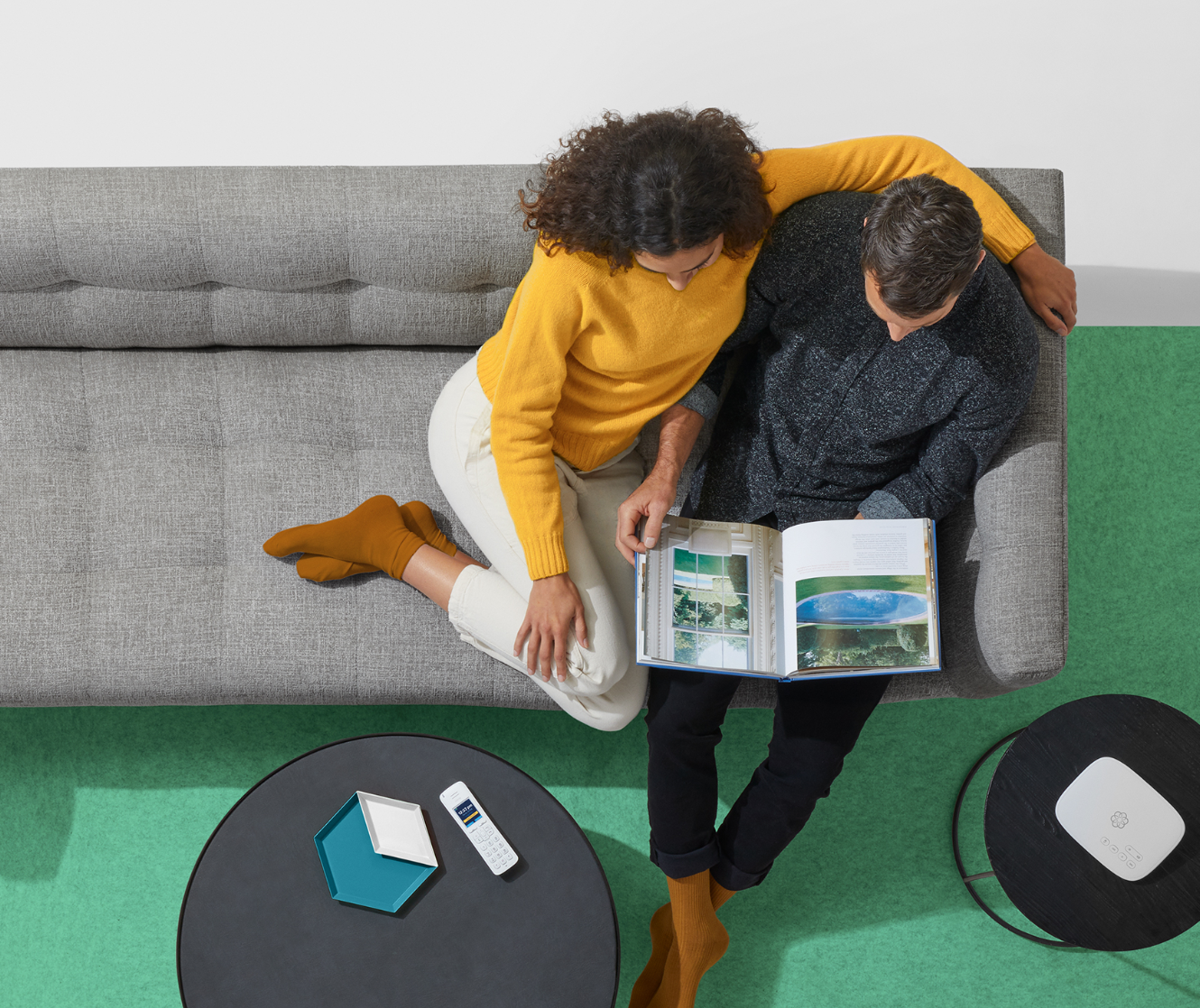 An image of a couple sitting down on sofa, telo handset on the side table