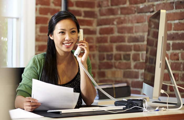 Business woman on the phone working with financial documents